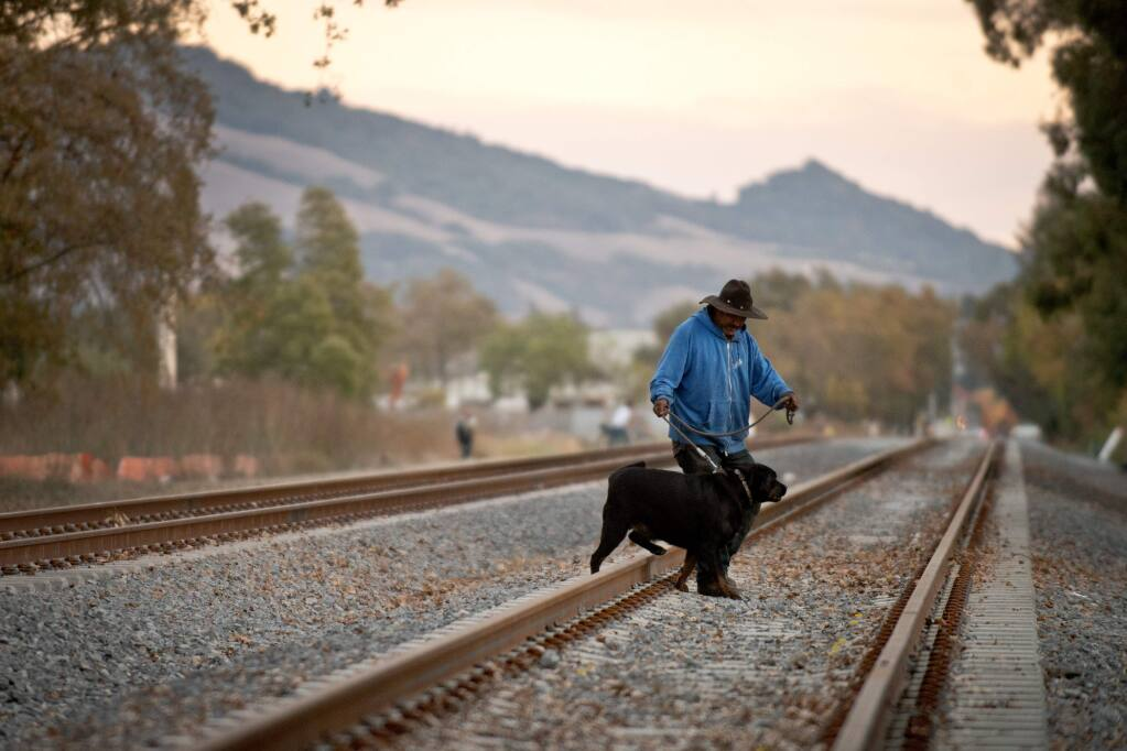 Jorge Robles walks his dog, Gordo, across railroad tracks that split Jennings Avenue near North Dutton Avenue in Santa Rosa in 2013. (ALVIN JORANDA/ PD FILE)