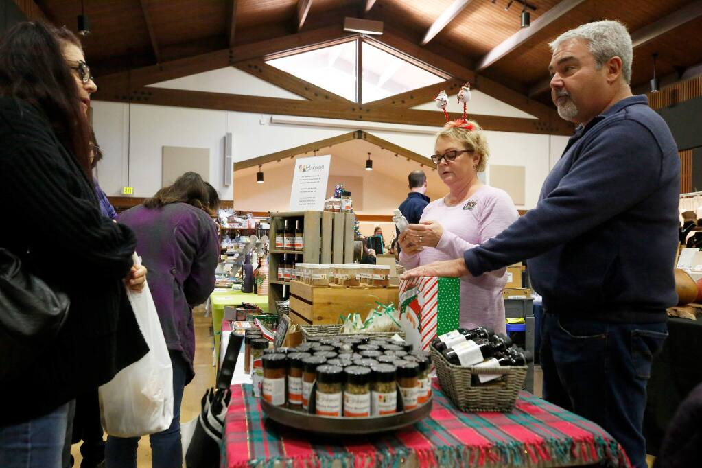 Phil and Heidi Schneider, right, owners of Berkmans Spices talk with customer Jacquie Lamica of Santa Rosa, who has ordered products online from Berkmans Spices, but made a purchase at their display table during the Holiday Arts and Crafts Faire at the Rohnert Park Community Center, in Rohnert Park, California, on Friday, November 29, 2019. (Alvin Jornada / The Press Democrat)