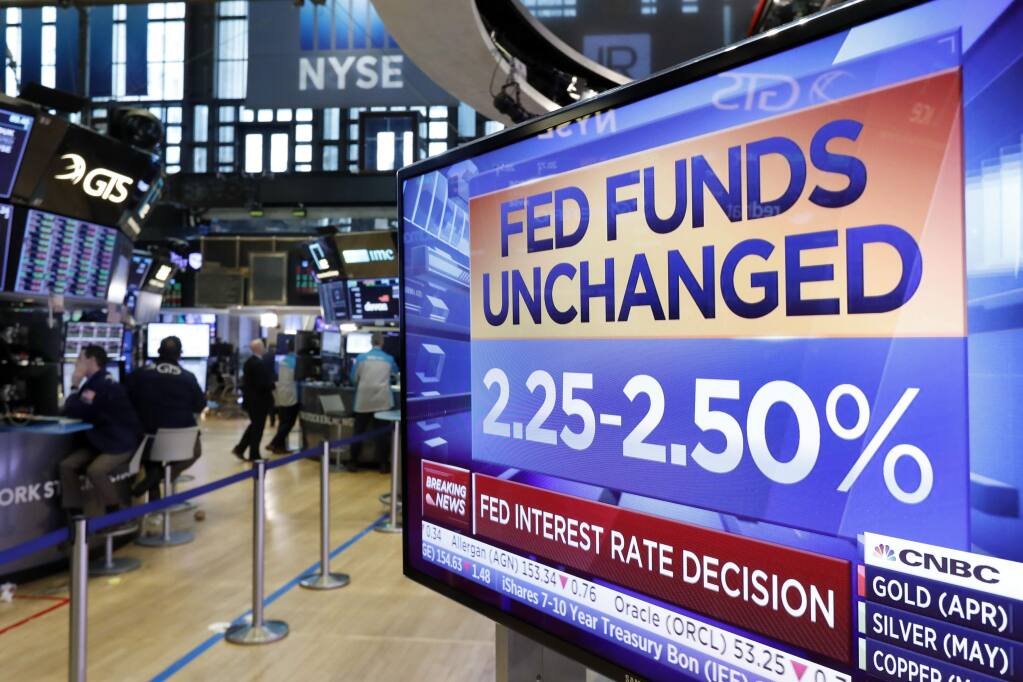 A screen on the floor of the New York Stock Exchange shows the rate decision of the Federal Reserve, Wednesday, March 20, 2019. The Federal Reserve is leaving its key interest rate unchanged and projecting no rate hikes in 2019, dramatically underscoring its plan to be 'patient' about any further increases. (AP Photo/Richard Drew)