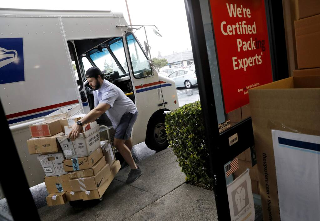 U.S. Postal worker John Sabia collects boxes to be shipped through the U.S. Postal Service at the UPS Store on W. College Ave. in Santa Rosa on Tuesday, December 18, 2018. (Beth Schlanker/The Press Democrat)