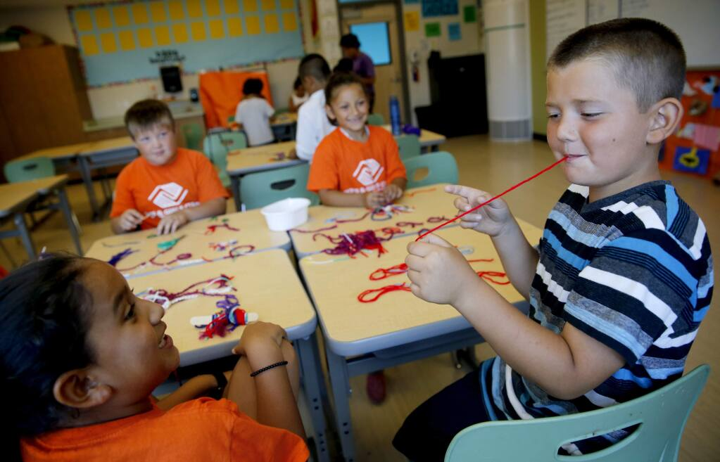 Nathan Ponce, 7, right, pulls a string out of his mouth as he jokes around with Natalie Ruiz, 7, left, Joseph Beall, 8, and America Diaz, 7, during the Boys and Girls Clubs of Central Sonoma County summer camp at Roseland Creek Elementary School in Santa Rosa, on Tuesday, July 14, 2015. (BETH SCHLANKER/ The Press Democrat)