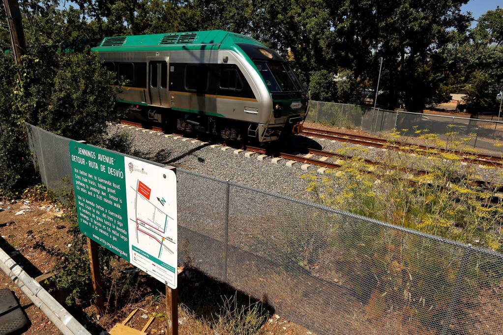 A SMART train passes between the two sides of Jennings Avenue, which does not have a crossing for pedestrian and bicycle traffic, in Santa Rosa, California, on Friday, July 27, 2018. The sign, at left, explains the detour to the nearest rail crossing at Guerneville Road where pedestrians and bicyclists can access the opposite side of Jennings Avenue. (Alvin Jornada / The Press Democrat)