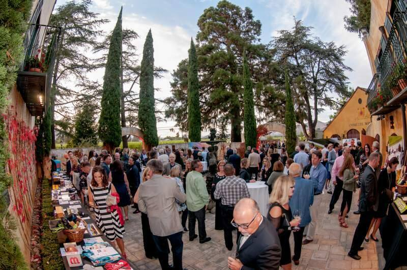 Speedway Children's Charities helped raise $76,000 during its IndyCar event this September. Above, attendees at the weekend's Andretti Winery fundraising dinner in Napa mull the silent auction items.