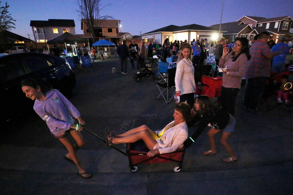 Fire survivor Leah Maikranz, 7, left, pulls her neighbor and teacher Anita Rackerby in a wagon around Jenna Place, with assistance from her neighborhood friend Talia Carey, 6, lower right, during Wine Wednesday, on the 2-year anniversary of the Tubbs Fire, in the Coffey Park neighborhood of Santa Rosa, California, on Wednesday, October 9, 2019. (Alvin Jornada / The Press Democrat)