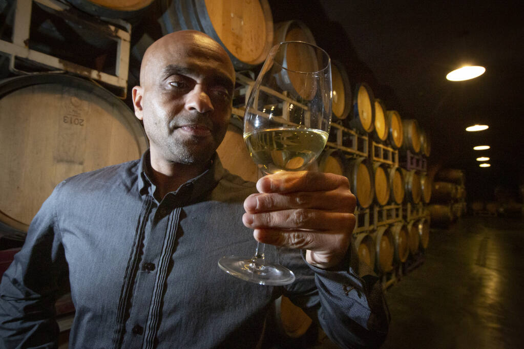 Winemaker Ayele Solomon, shown here at the Deerfield Ranch wine caves on Jan. 29, examines a glass of his honey wine, a type of wine historically made by every culture in the world, alongside barrels containing the beverage. (Photo by Robbi Pengelly/Index-Tribune)