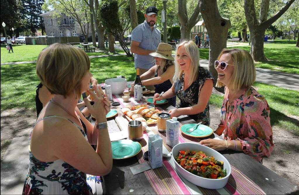 Allyson Weekes, second from right, and her husband Nigel Weekes, standing, serve lunch to friends Jacqui Kotula, right, Lisa Hanson, and Angela Martin in Sonoma Plaza, after taking them wine tasting at Three Sticks Wines on Monday, April 22, 2019. Allyson and Nigel Weekes own Bohemian Highway Tourism Company.(Christopher Chung/ The Press Democrat)