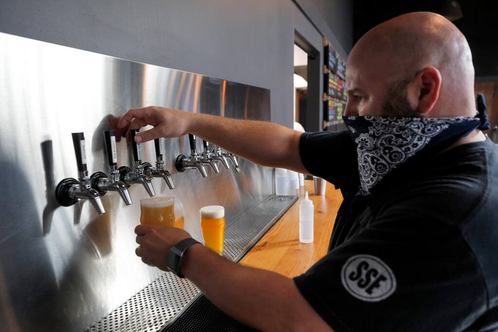 Brewer/co-owner Chris Adamian pours beer for a customer's order at Corner Project Ales and Eats in Geyserville, California, on Friday, July 31, 2020. (Alvin Jornada / The Press Democrat)