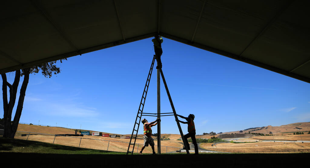 In preparation for June's NASCAR event at Sonoma Raceway, Jonathan Rodriguez, left, and Kevin Samayoa of Special Event Work Solutions steady a support beam as Jose Samayoa bolts it to a larger tent structure, Wednesday, May 12, 2021 in Sonoma along the straightaway to turn two. (Kent Porter / The Press Democrat) 2021