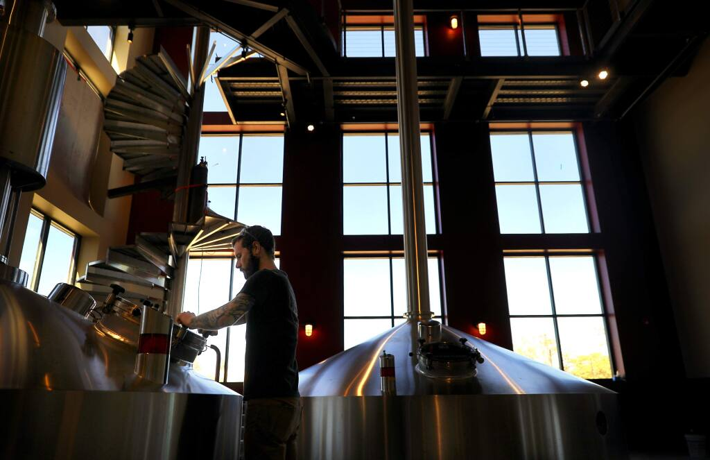Lead brewer Zach Kelly prepares to add hops to a tank of Consecration in the brew house of the new Russian River Brewing Company brewery and restaurant facility, under construction in Windsor on Monday, September 17, 2018. (Christopher Chung/ The Press Democrat)