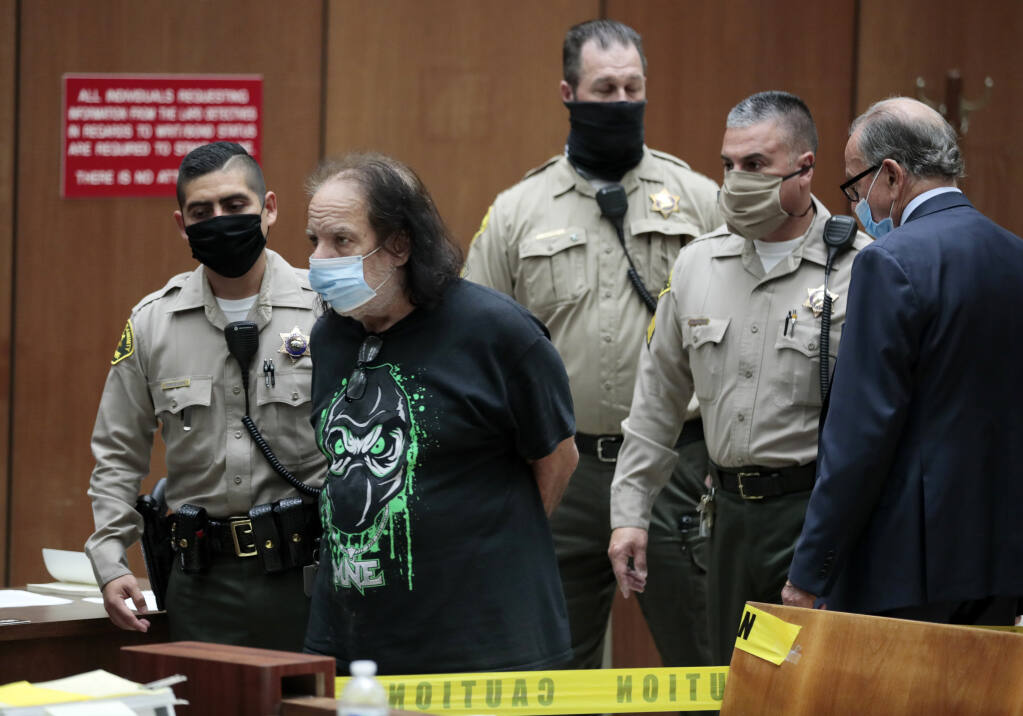 Adult film star Ron Jeremy appears in court with his attorney Stuart Goldfarb, right, upon being charged with sexually assaulting four women in Dept. 30 at LA Superior Court in Los Angeles on Tuesday, June 23, 2020.    Los Angeles County prosecutors say Jeremy has been charged with raping three women and sexually assaulting a fourth. (Robert Gauthier / Los Angeles Times via AP, POOL)