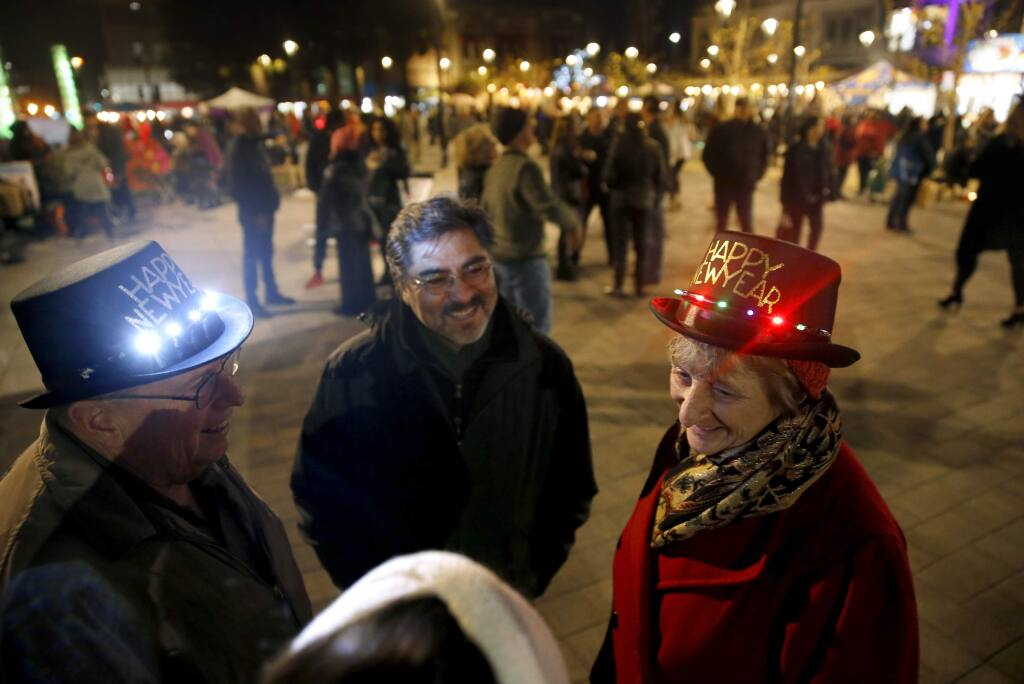 (Clockwise from right) Teresa Denniston celebrates New Years Eve with Tina Gomez, bottom, her husband Rick, left, and Dan Gomez, center, at Old Courthouse Square in Santa Rosa, on Sunday, December 31, 2017. (BETH SCHLANKER/ The Press Democrat)