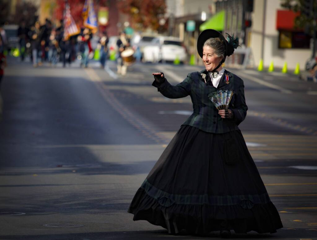 Cindy Eddy of the Sonoma County Auxiliary to Sons of Union Veterans of Civil War waves to the crowds that gathered to celebrate and honor Veterans Day in downtown Petaluma on Nov. 11, 2019. (Crissy Pascual/Argus-Courier)