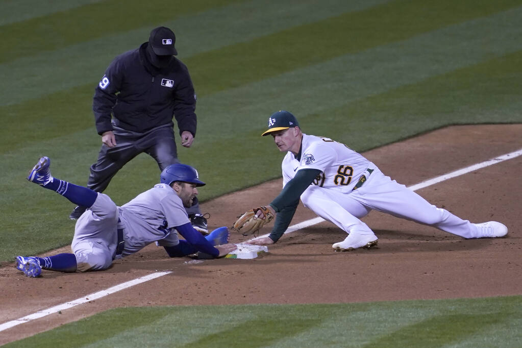 Los Angeles Dodgers' Chris Taylor, bottom left, slides safely into third base next to Oakland Athletics third baseman Matt Chapman during the third inning of a baseball game in Oakland, Calif., Monday, April 5, 2021. Umpire Sean Barber, top left, looks on. (AP Photo/Jeff Chiu)