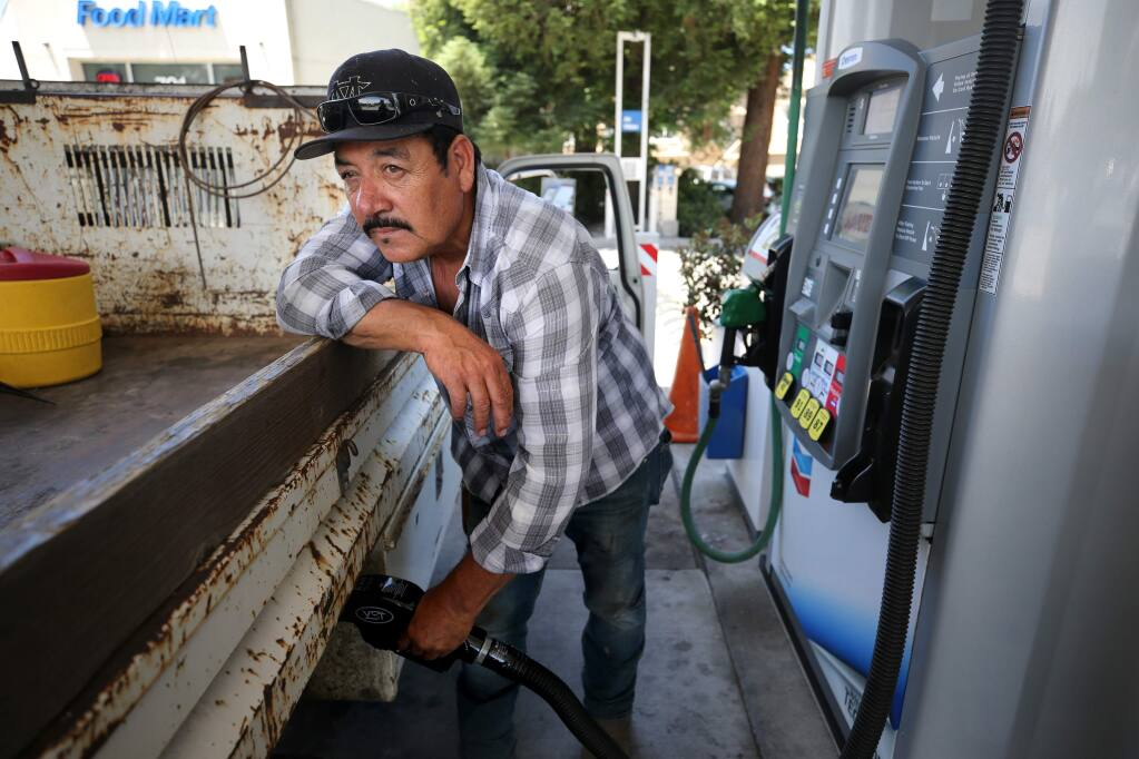 Refugio Arreguin fills up his tank at the Chevron station on the corner of College and Mendocino avenues in Santa Rosa on Monday, June 24, 2019. (BETH SCHLANKER/ The Press Democrat)