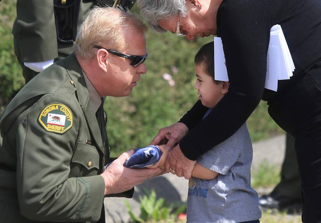Mike Vail, president of the Sonoma County Deputy Sheriff's Association presents an American flag to Barbara Trejo and her great grandson Jordan Bacigalupi, 3, after a ceremony in remembrance for her husband, Sonoma County Sheriff's Deputy Frank Trejo, 58, who was one year away from retirement when he was killed on March 29, 1995 by newly paroled convict Robert Scully. Area law enforcement gathered at the site of Trejo's death to pay their respect, Wednesday March 29, 2017 on Hwy. 12 between Santa Rosa and Sebastopol. Kent Porter / Press Democrat) 2016