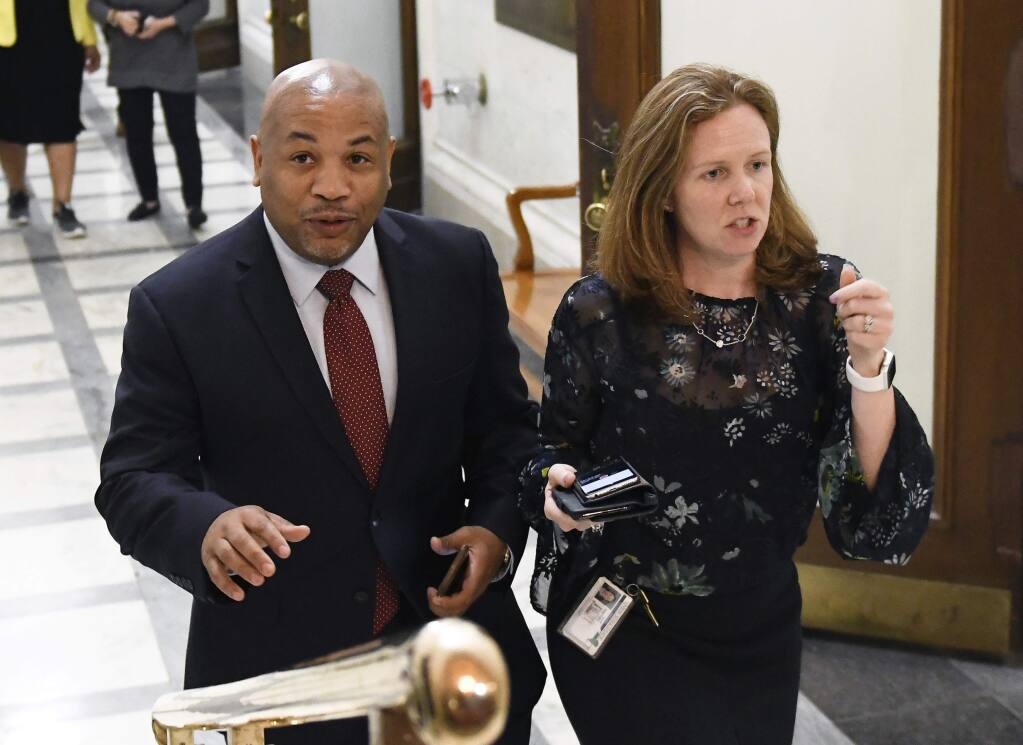 New York Assembly Speaker Carl Heastie, D-Bronx, left, walks with staff member Kerri Biche before talking with reporters about New York Attorney General Eric Schneiderman's resignation at the state Capitol Tuesday, May 8, 2018, in Albany, N.Y. Four women accused Schneiderman of physical violence in a New Yorker article published Monday evening. (AP Photo/Hans Pennink)