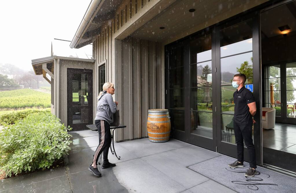 Wine club member Debra Kazarian picks up her wine curbside at the Robert Young Estate Winery tasting room, while greeted by Robert Young II, near Geyserville on Monday, May 11, 2020. (Christopher Chung/ The Press Democrat)