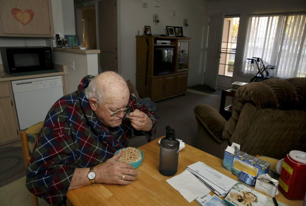 Wayne Martinez eats his breakfast at his kitchen table where a stack of unpaid bills sits at the Vintage Park Senior Apartments in Santa Rosa, on Thursday, March 26, 2015. (BETH SCHLANKER/ The Press Democrat)