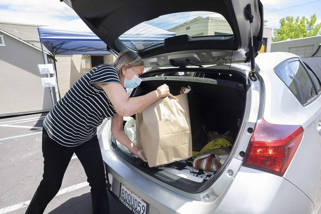 Sandy Piotter, the executive director of Friends in Sonoma Helping (F.I.S.H.), loads a bag of groceries into a car for contactless pickup for those in need. (John Burgess/The Press Democrat).
