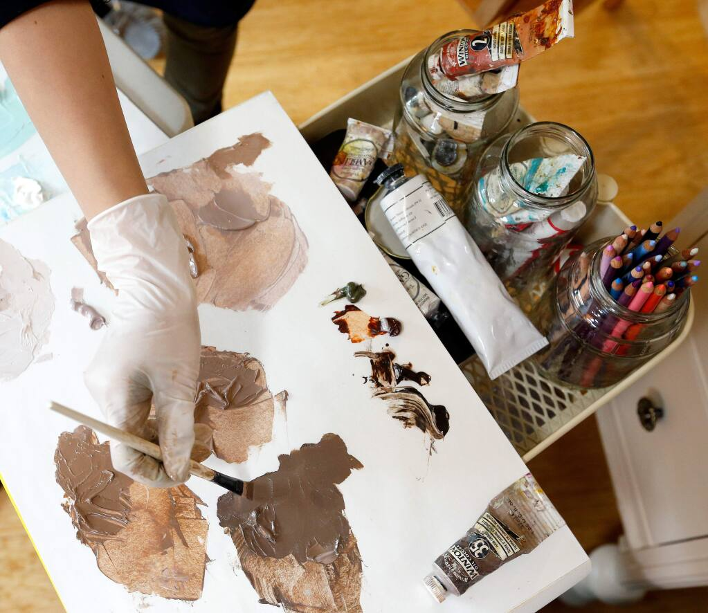 Artist Dayana Leon works on a painting at her home studio in Santa Rosa, California, on Wednesday, April 12, 2017. Leon's current body of work explores the concept of 'typical' beauty standards. (Alvin Jornada / The Press Democrat)