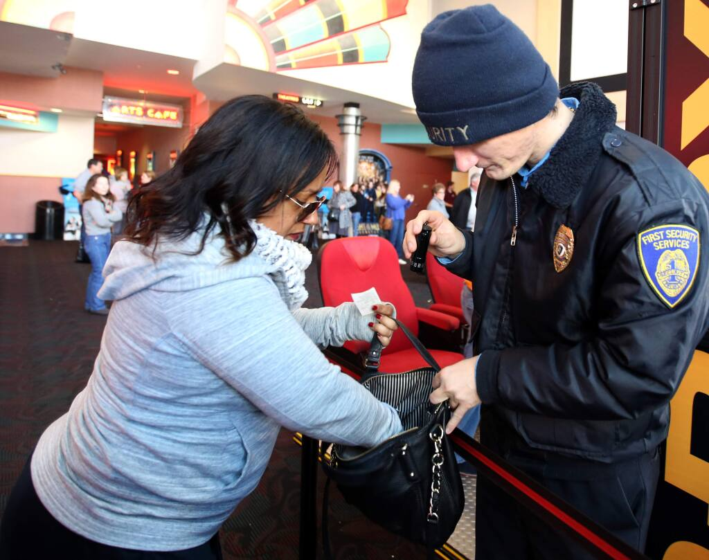 FILE - Security guard Thomas Tilley, right, searches the bag of Tracy Low, left, at the Boulevard 14 Cinemas in Petaluma, Thursday, December 25, 2014. (Crista Jeremiason / The Press Democrat)