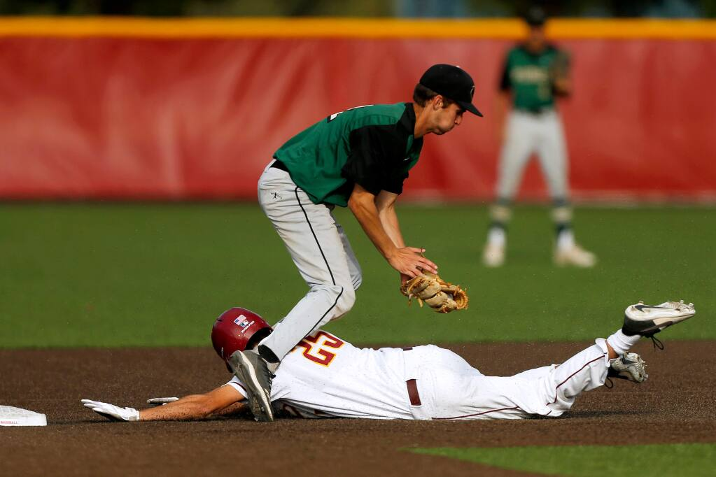 Cardinal Newman's Nick George (25) slides between the legs of Maria Carrillo's KC Kelly (22) and reaches second base safely before being tagged, during a varsity baseball game between Maria Carrillo and Cardinal Newman high schools in Santa Rosa, California, on Friday, May 10, 2019. (Alvin Jornada / The Press Democrat)
