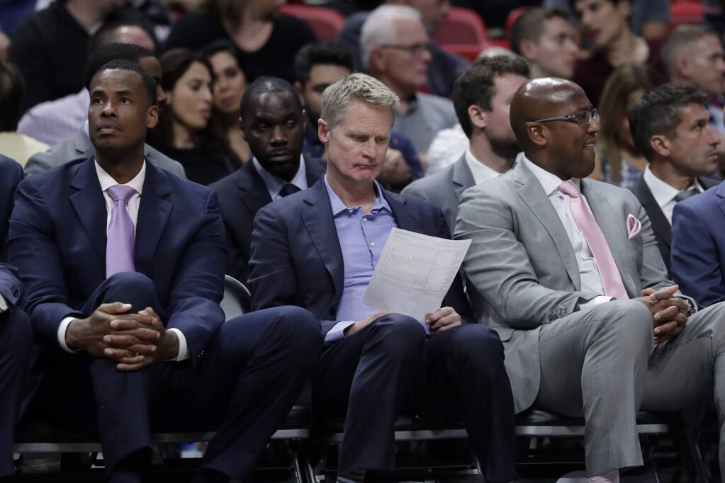 Golden State Warriors head coach Steve Kerr, center, sits with assistant coaches Jarron Collins, left, and Mike Brown, right, during the second half against the Miami Heat, Friday, Nov. 29, 2019, in Miami. The Heat won 122-105. (AP Photo/Lynne Sladky)