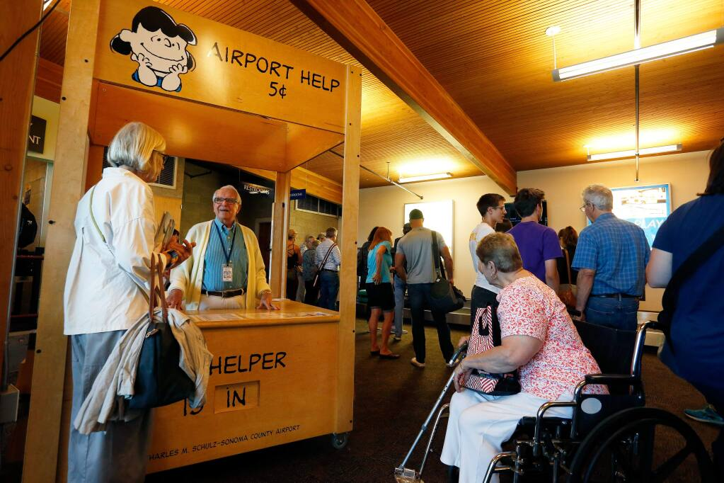 Airport volunteer Ken Hicks, second from left, answers questions for travelers at Charles M. Schulz-Sonoma County Airport in Santa Rosa, California, on Tuesday, July 11, 2017. Airport officials are planning to double the size of Gate 2, add more parking spaces and build a new 28,000 square foot terminal in the future. (Alvin Jornada / The Press Democrat)