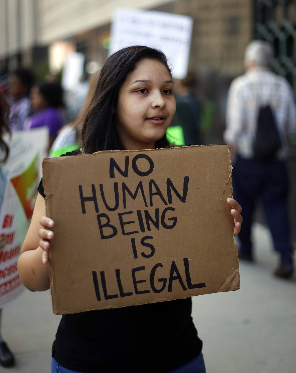 FILE - In this May 16, 2017 file photo, Alex Linders, a junior at Pioneer High School in Ann Arbor, Mich., carries a sign during a rally outside a federal courthouse in Detroit. For years, immigrants have checked in regularly with federal deportation agents to show they've been following the country's laws even though they have been ordered to leave. Now, in cases spanning from Michigan to California, many of those who have exhausted their legal options are being told their time here is up. (AP Photo/Paul Sancya, File)