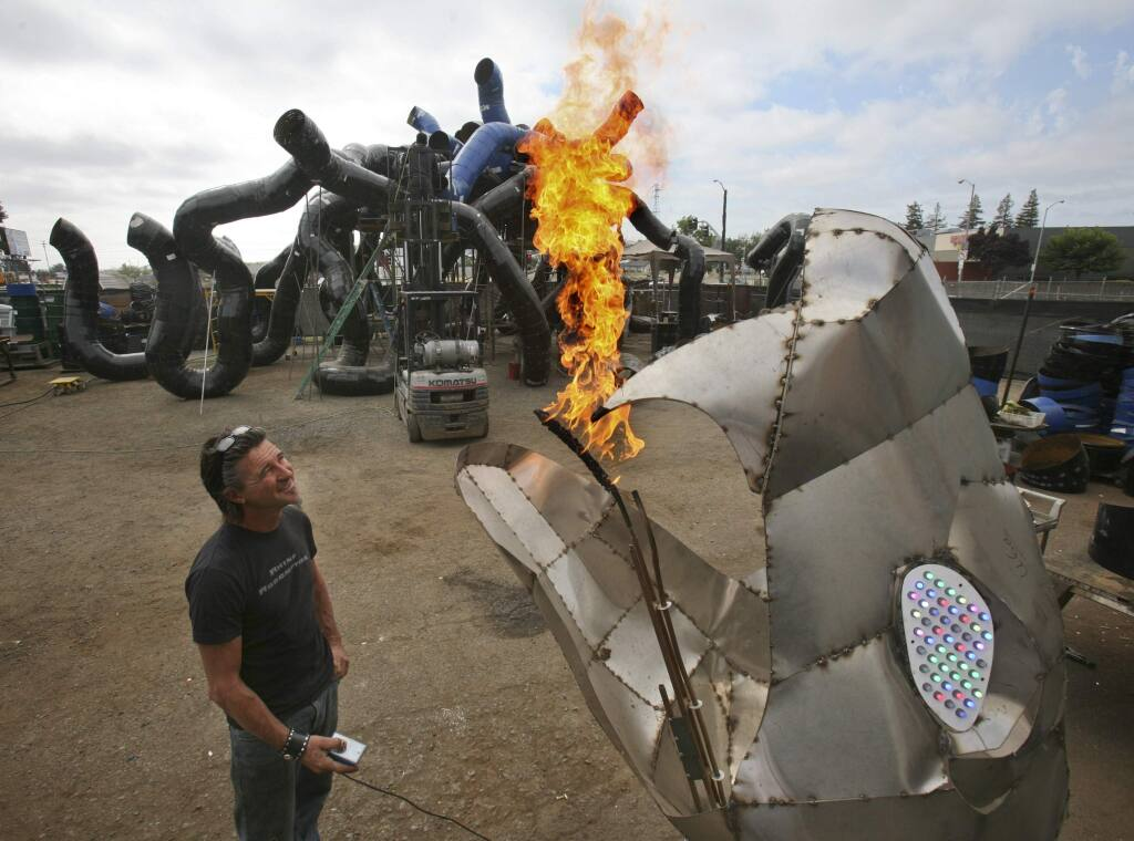 Kevin Clark tests one of the flame throwing fire-breathing snake heads for his giant fire-breathing Medusa seen in the background that he is building for this years Burning Man at his shop in Petaluma on Saturday August 1, 2015.(SCOTT MANCHESTER/ARGUS-COURIER STAFF)