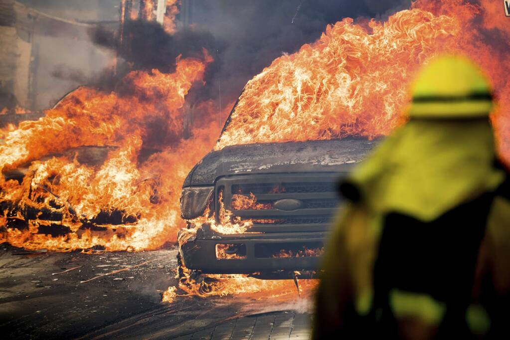 Flames consume vehicles as a wildfire rages in Ventura, Calif., on Tuesday, Dec. 5, 2017. (AP Photo/Noah Berger)