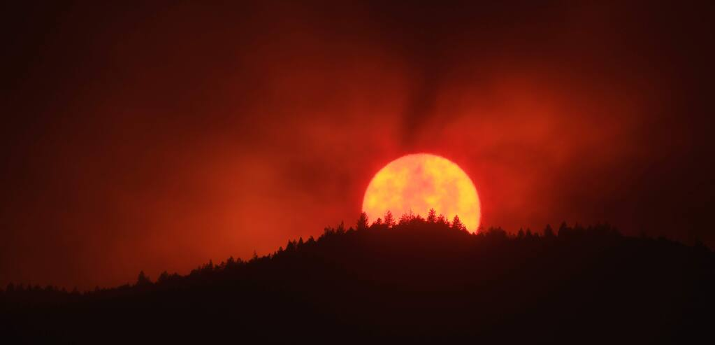 Thick smoke from the Kincade fire obscures the setting sun as seen from the Middletown side of the Mayacamas Mountains, Friday, Oct. 25, 2019. (Kent Porter / The Press Democrat) 2019