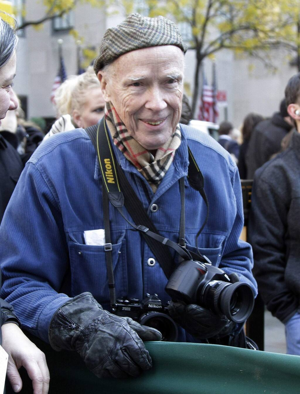 FILE - In this Nov. 11, 2011 file photo, New York Times photographer Bill Cunningham waits for the arrival of the annual Rockefeller Center Christmas tree, in New York. Cunningham, a longtime fashion photographer for The New York Times known for taking pictures of everyday people on the streets in New York died on Saturday, June 25, 2016, after suffering a stroke in New York. He was 87. (AP Photo/Richard Drew, File)