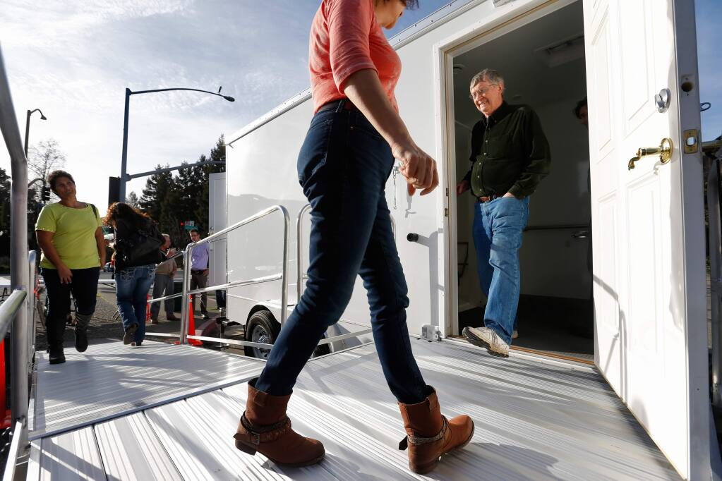 Roseanna Gonzalez, left, and Marge Lopez, center, and Lee Dibble, right, take turns looking inside the new portable bathroom-shower trailer, part of the Homeless Outreach Services Team (HOST) program run by Catholic Charities during the trailer's unveiling in front of city hall in Santa Rosa, California on Friday, February 12, 2016. (Alvin Jornada / The Press Democrat)