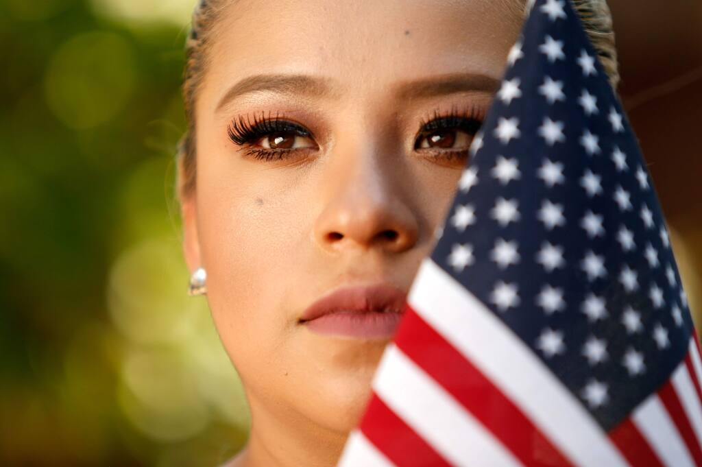 Amalia Montes, 26, a Dreamer enrolled in the Delayed Action for Childhood Arrivals (DACA) program, poses for a portrait with an American flag that was displayed at her home, in Santa Rosa, California on Tuesday, September 5, 2017. Montes came to the United States at age 15, with her mother and younger sister. (Alvin Jornada / The Press Democrat)