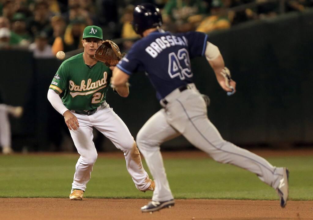 Matt Chapman reels in a liner as Mike Brosseau of Tampa Bay runs, Wednesday, Oct. 2, 2019 in Oakland. (Kent Porter / The Press Democrat)