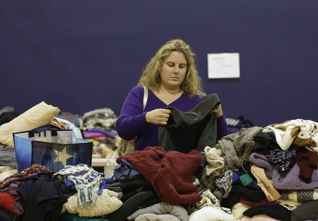 Jenna Latrache looks through clothes at a donation center for victims of the recent wildfires, Tuesday, Oct. 17, 2017, in Santa Rosa, Calif. Latrache lost her Coffey Park home when she and her family had to evacuate a week ago as a massive wildfire swept through the area. (AP Photo/Rich Pedroncelli)