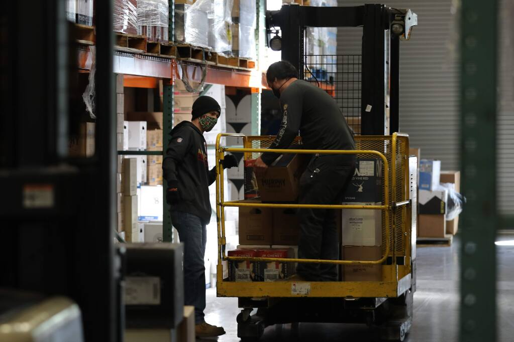 Oliver's Market warehouse employees Nicholas Hill, left, and Cody Harrington fill orders at the warehouse in Santa Rosa, California on Tuesday, April 14, 2020. (BETH SCHLANKER/ The Press Democrat)