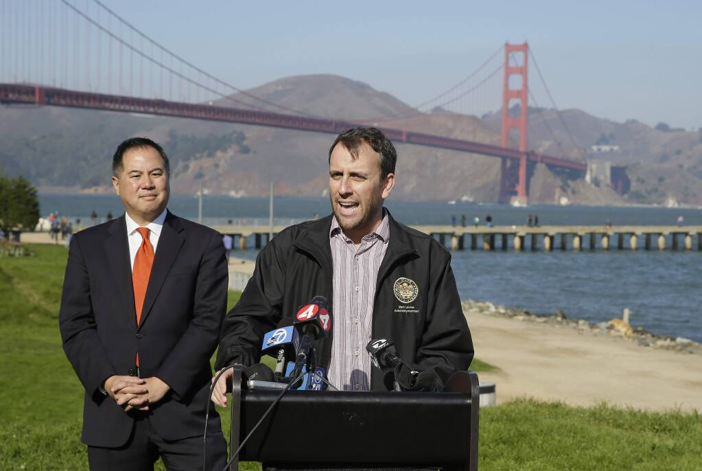 State assembly members Phil Ting, left, and Marc Levine, at podium, speak out against sidewalk tolls with the Golden Gate Bridge in the background during a press conference at Crissy Field Tuesday, Nov. 25, 2014, in San Francisco. (AP Photo/Eric Risberg)