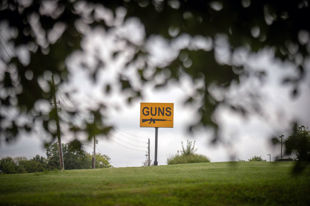 """A sign outside a gun shop and shooting range in Blue Springs, Mo., on Sept. 3, 2021. Missouri's Second Amendment Preservation Act declares that state firearms laws """"exceed"""" the federal government's power to track, register and regulate guns and gun owners. (Christopher Smith/The New York Times)"""