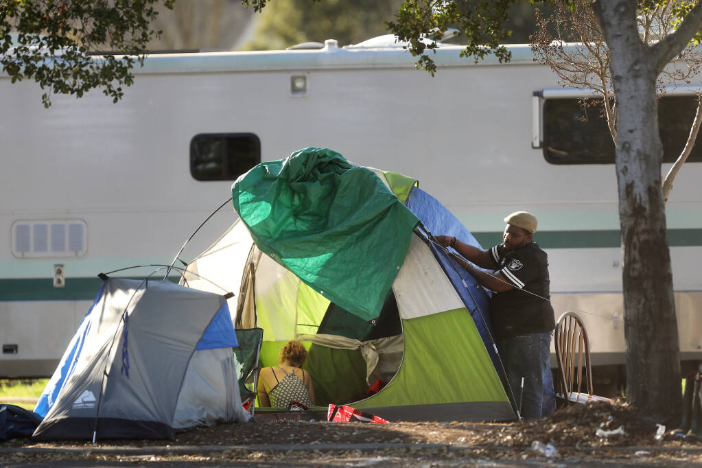 A man named Will makes adjustments to a tent at the homeless encampment on Industrial Dr. in Santa Rosa, Calif., on Monday, January 18, 2021. (BETH SCHLANKER/ The Press Democrat)