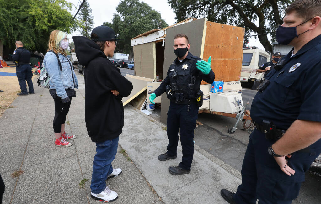 Santa Rosa Police Officer Tim Barrett explains to Michael Howard why his mother's trailer is being towed from Fremont Park, on Fifth Street, in Santa Rosa on Wednesday, July 29, 2020.  (Christopher Chung / The Press Democrat)