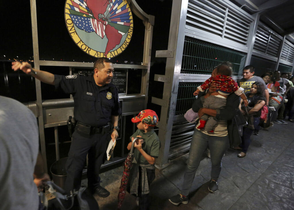 FILE - In this Sept. 17, 2019, file photo, a U.S. Customs and Border Protection officer gives instructions to migrants who are on their way to apply for asylum in the United States, on International Bridge 1 as they depart Nuevo Laredo, Mexico. A federal judge on Monday, Aug. 31, 2020, blocked U.S. Customs and Border Protection employees from conducting the initial screening for people seeking asylum, dealing a setback to one of the Trump administration's efforts to rein in asylum. (AP Photo/Fernando Llano, File)