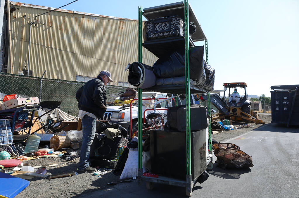 Rich, who declined to give his last name, begins packing up his belongings as the homeless encampments along Yolanda Avenue are removed in Santa Rosa on Thursday, May 6, 2021.  (Christopher Chung/ The Press Democrat)