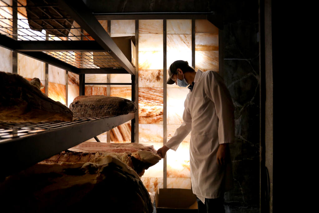 Ryan Taylor co-owner Panizzera Meat Co. goes inside a meat locker lined with salt blocks used for humidity control in Occidental on Tuesday, Aug. 3, 2021. (Beth Schlanker / The Press Democrat)