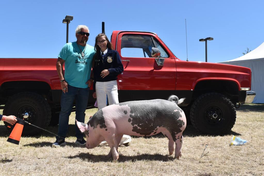 Guy Fieri, FFA senior member Frances Marshall and Chevy, the pig which Fieri purchased at Sunday's auction. (Heidi Mickelson)