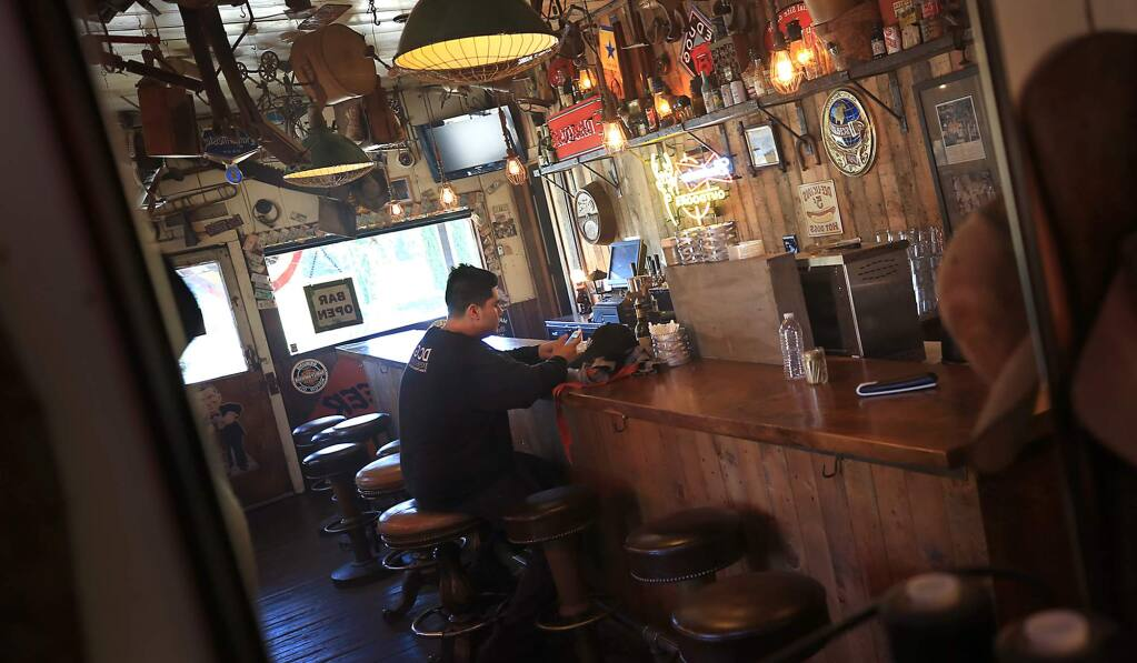 A Dry Creek General Store employee takes a break at the closed bar on Thursday, July 6, 2017. (KENT PORTER/ PD)