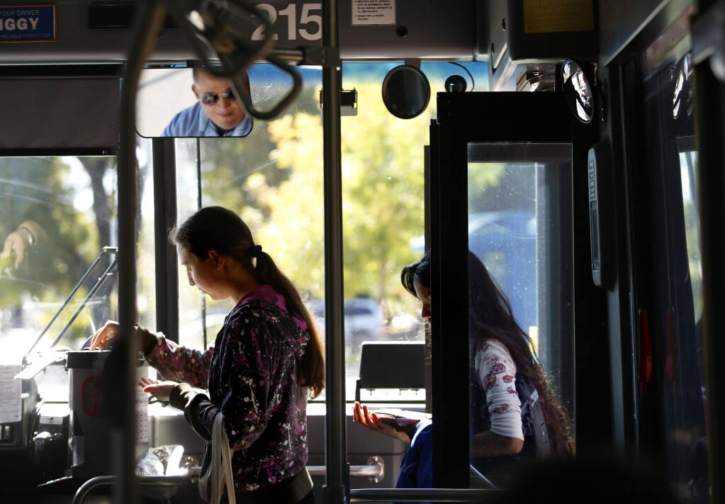 A Santa Rosa Junior College student Olivia boards a Sonoma County Transit bus at the bus stop on Mendocino at Pacific avenues in Santa Rosa. (BETH SCHLANKER / The Press Democrat, 2014)