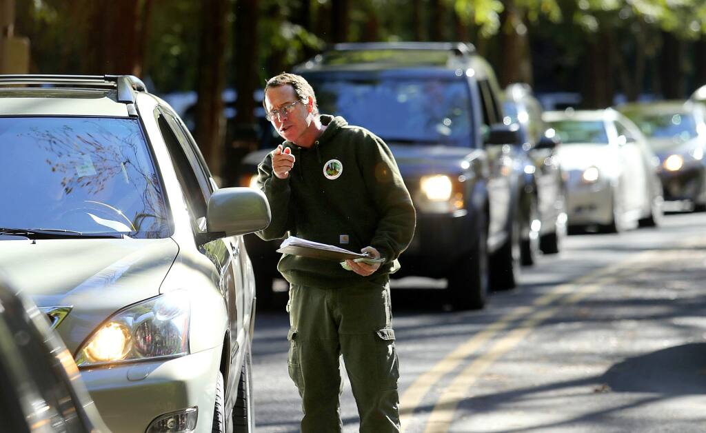 Craig Wilkinson, with the Stewards of the Coast and Redwoods, collects free passes offered by the group from a line of cars at Armstrong Woods State Park on the day after Thanksgiving. (JOHN BURGESS / The Press Democrat)