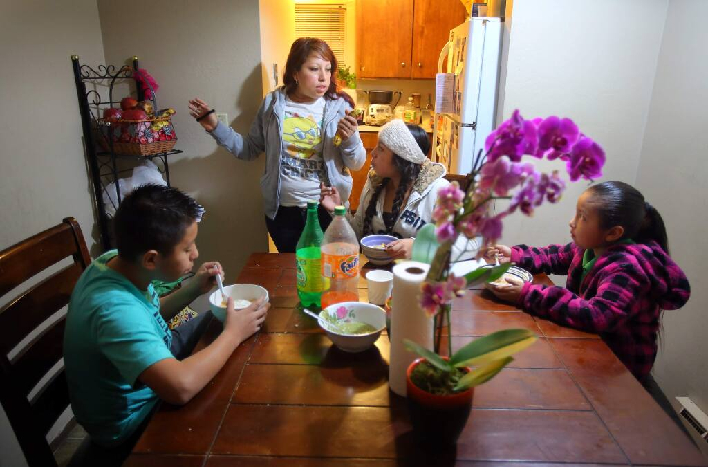 Karla Orozco, standing, talks with her children, Jobani Sanchez, 12, left, Janet Sanchez, 15, and Jacquline Sanchez, 7, as they eat breakfast in their apartment before heading off to school in Santa Rosa on Friday, January 16, 2015. Code enforcement officers confirmed that the families living in the the ten-unit Hoen Avenue apartment complex have been plagued by rodent and cockroach infestations, dangerous levels of mold, and other substandard conditions.(Christopher Chung/ The Press Democrat)